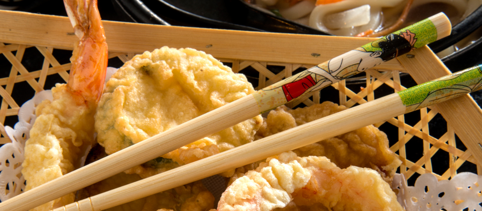 A basket of shrimp with chop sticks laying diagonally across the food